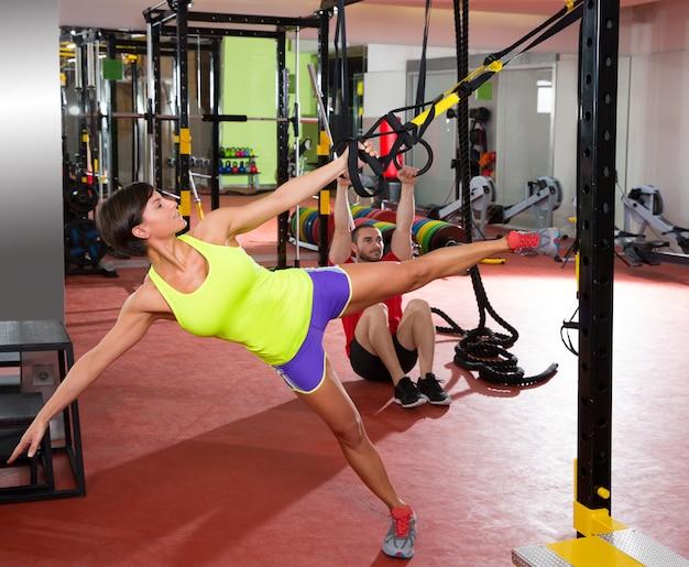Fitness trx-trainingsoefeningen bij gym vrouw en man