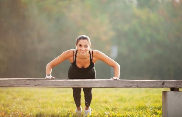 Fitness. van sport, recreatie en motivatie. atletische vrouw die zich in plankpositie in openlucht bij zonsondergang bevinden