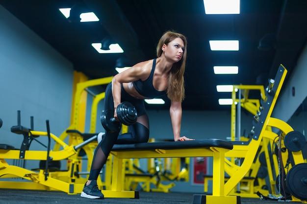 Fitness vrouw die oefening met domoor doet die op sportbank leunt in een moderne gymnastiek.