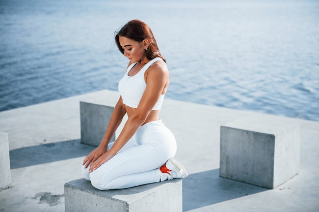 Fitness vrouw die overdag uitrust in de buurt van het meer