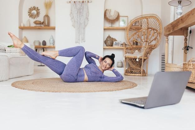 Fitness vrouw die thuis traint en wendingen abs oefeningen doet.