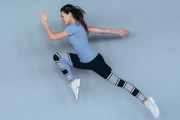 Fitness vrouw die thuis traint, springt en rent, intensieve oefeningen doet.
