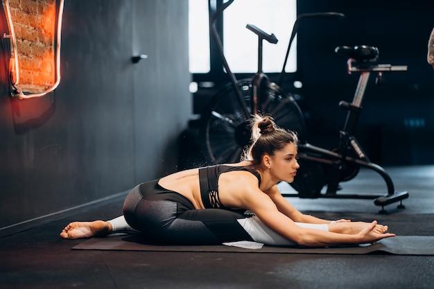 Fitness vrouw die zich uitstrekt doen pilates strekt zich uit oefeningen in de sportschool.