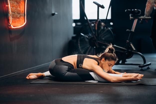 Fitness vrouw die zich uitstrekt doen pilates strekt zich uit