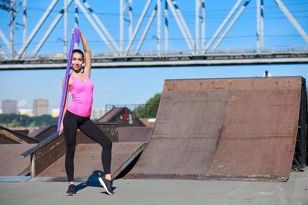 Fitness vrouw doen rekoefeningen met elastische rubberen band op stedelijke stad