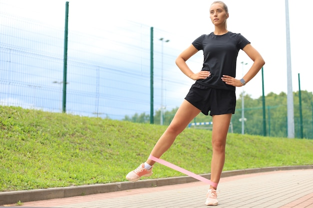 Fitness vrouw doet beenoefeningen met fitness kauwgom in park.