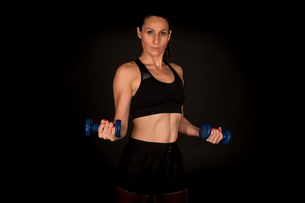 Fitness vrouw doet biceps met halters