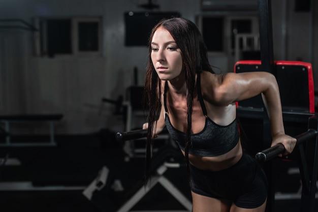 Fitness vrouw doet push-ups op ongelijke balken in crossfit gym,