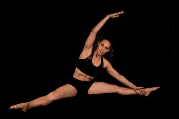 Fitness vrouw doet stretching op de vloer met armen