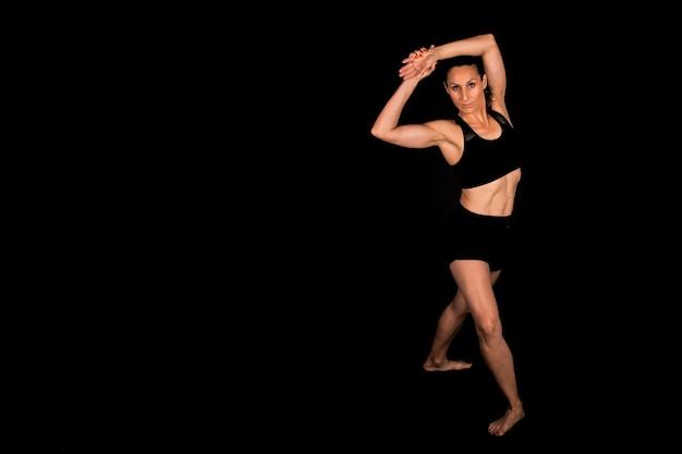 Fitness vrouw doet yoga die zich uitstrekt op zwarte achtergrond