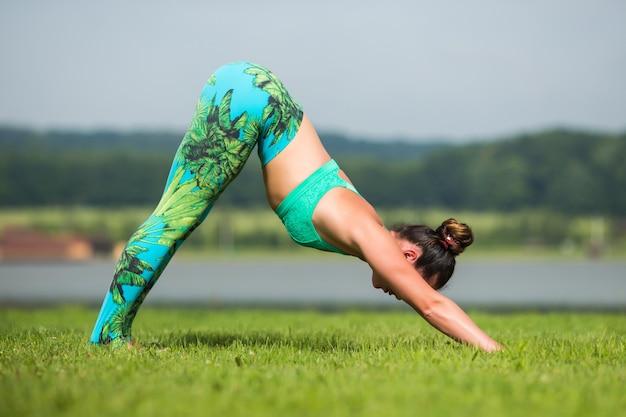Fitness vrouw doet yoga oefening en ontspannen met sportkleding in groen park in de zomer