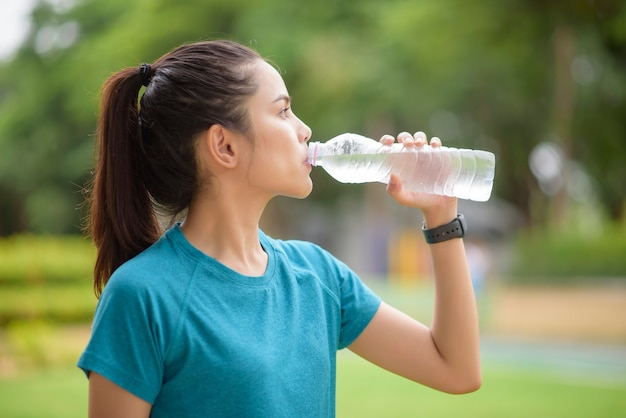 Fitness vrouw drinkwater na training in park