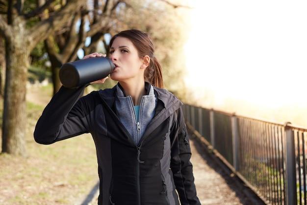 Fitness vrouw drinkwater uit een fles na training