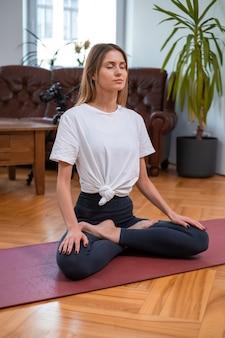 Fitness vrouw gericht op haar yoga workout poses op mat in modern appartement overdag. gezondheid en lichaamsverzorging.