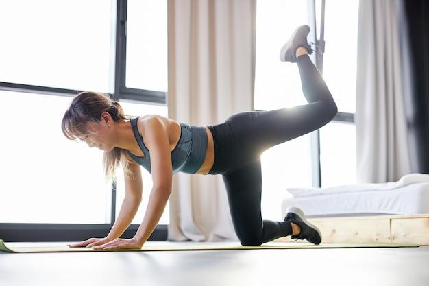 Fitness vrouw in trainingspak doet oefeningen op mat vloer, jonge vrouw houdt zich bezig met sport, leidt een gezonde levensstijl