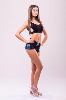 Fitness vrouw. jong sportief kaukasisch vrouwelijk model dat op witte achtergrond in volledig lichaam wordt geïsoleerd