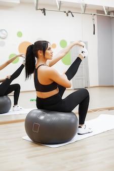 Fitness vrouw. jonge aantrekkelijke vrouw die oefeningen doet die bal gebruiken