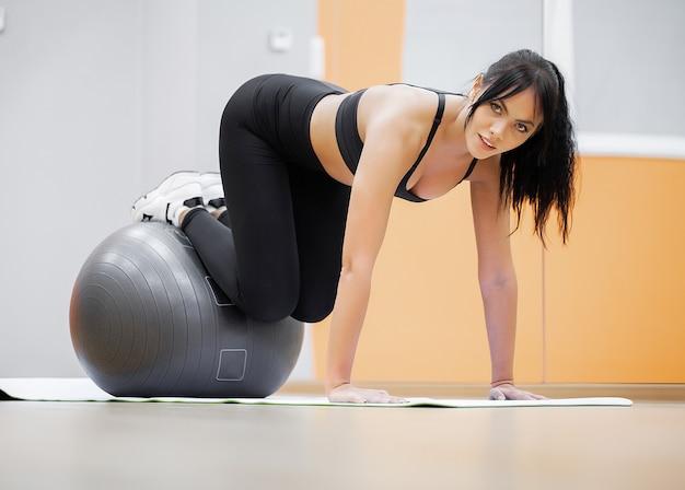 Fitness vrouw. jonge aantrekkelijke vrouw die opdrukoefeningen doet die bal gebruiken.