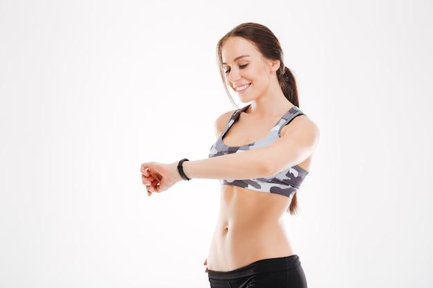 Fitness vrouw kijken naar horloge in studio. bovenaanzicht. geïsoleerd
