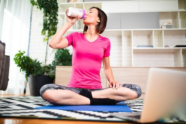 Fitness vrouw kijkt naar online tutorials op laptop tijdens het sporten in de woonkamer thuis.