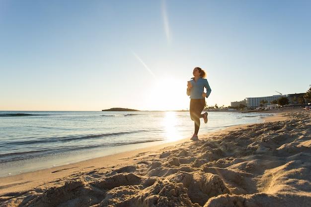 Fitness vrouw loopt door de oceaan bij zonsondergang.