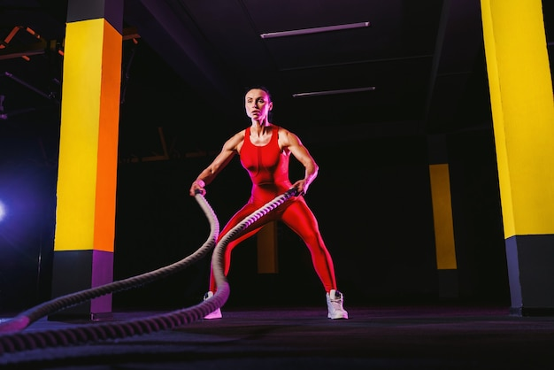 Fitness vrouw met behulp van trainingskabels voor oefening in de sportschool. atleet uit te werken met touwen van de strijd bij cross gym.