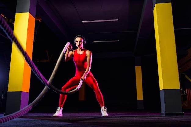 Fitness vrouw met behulp van trainingskabels voor oefening in de sportschool. atleet uit te werken met touwen van de strijd op sportschool.