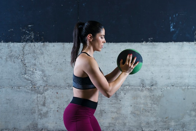 Fitness vrouw met medicijnbal en trainen in de sportschool