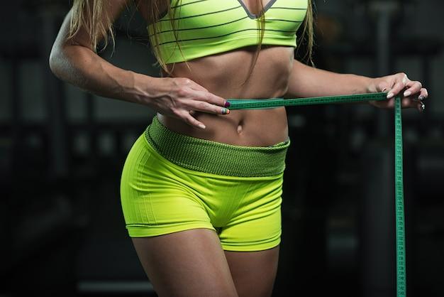 Fitness vrouw met roulette meet de omtrek van de buik