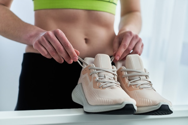 Fitness vrouw met slim fit sportkleding dragen beige sneakers voor joggen en hardlopen training. sport en wees fit. sportmensen met een gezonde sportieve levensstijl