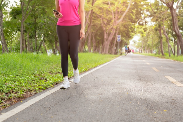 Fitness vrouw oefening lopen op park parcours met hand met mobiele telefoon.