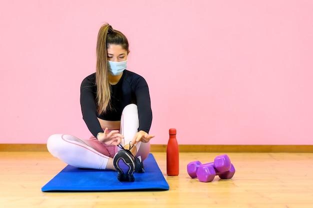 Fitness vrouw streching ontspannen na de training en het dragen van een beschermend gezichtsmasker tijdens covid 19