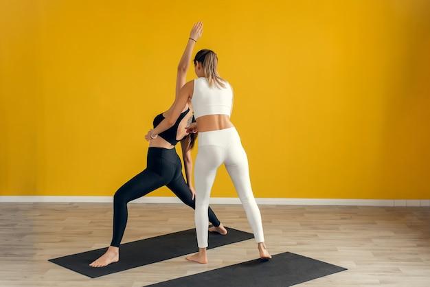 Fitness vrouw training met haar personal trainer op sportschool. jong stel doet rekoefeningen
