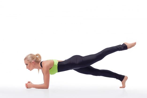 Fitness vrouw uit te werken planking oefening doet