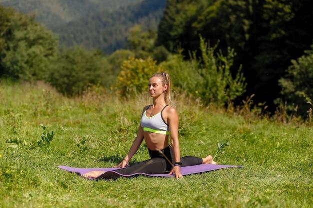 Fitness vrouw zitten in een yoga pose in een park. vrouw beoefenen van yoga zittend in een park met palmen samengevoegd. in een touw zitten. yoga en stretchen