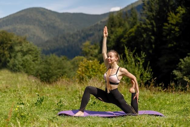 Fitness vrouw zitten in een yoga pose in een park. vrouw beoefenen van yoga zittend in een park met palmen samengevoegd. yoga en stretchen