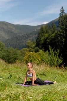 Fitness vrouw zitten in een yoga pose in een park. vrouw beoefenen van yoga zittend in een park met palmen samengevoegd. zittend in de vloer touw. yoga en stretchen