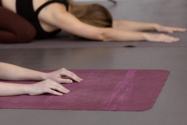 Fitness vrouwelijke groep doet oefenen in een yogales