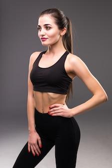 Fitness vrouwelijke vrouw met gespierd lichaam klaar voor training op grijze muur