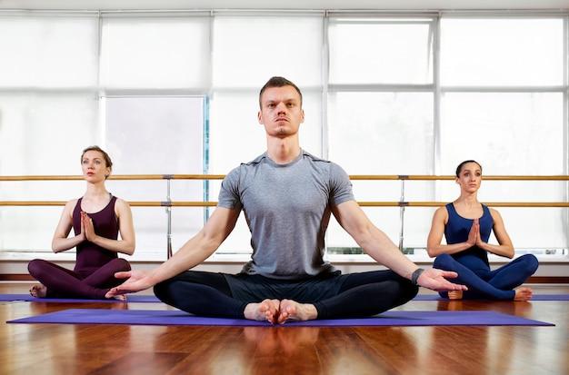 Fitness, yoga en gezond levensstijlconcept - de groep mensen die lotusbloemverbindinggebaar doen en in gezeten mediteren stelt