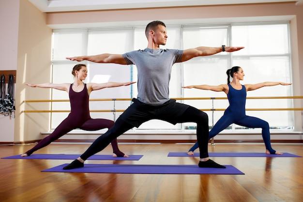 Fitness, yoga en gezonde levensstijl - een groep mensen die oefeningen doet voor stretchen en mediteren in verschillende yogahoudingen.