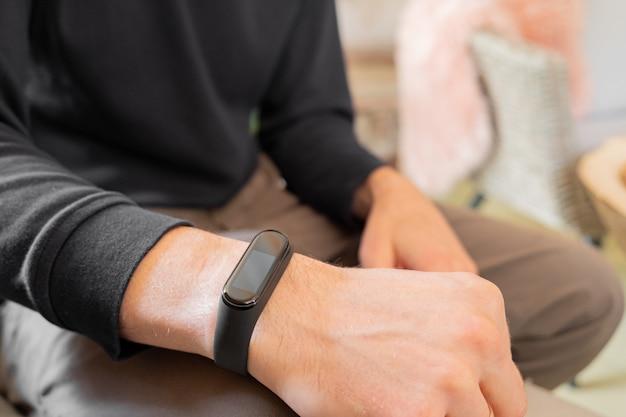 Fitnessband op de handweergave van de mens van de pols van de man met een slim horloge erop