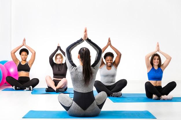 Fitnessclas op yogapositie op mat