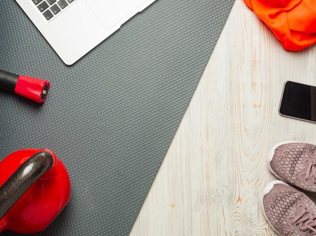 Fitnessconcept sport en fitness thuis laptop, bodybar, rode kettlebell, grijze mat, houten lichte vloer