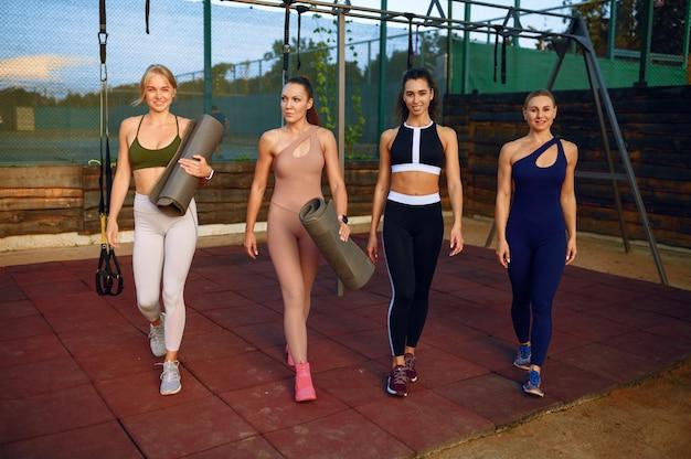 Fitnessgroep voor vrouwen op sportveld, vooraanzicht, training buitenshuis