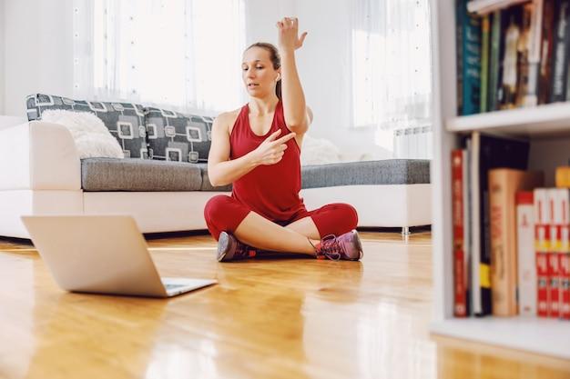 Fitnessinstructeur die thuis op de grond zit en oefeningen uitlegt aan de student