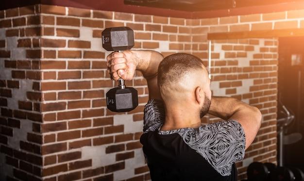 Fitnessinstructeur in de sportschool. fitness man doet oefeningen in de sportschool. fitness en gezond levensstijlconcept.
