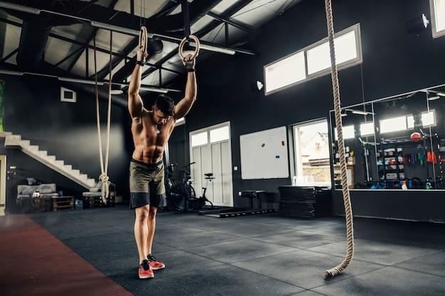 Fitnessman staat met een naakt bovenlichaam midden in de sportschool en laat zijn handen op hoepels rusten