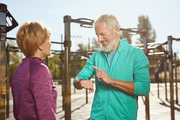 Fitnessresultaten controleren gelukkige senior man in sportkleding kijken naar smartwatch en glimlachen terwijl