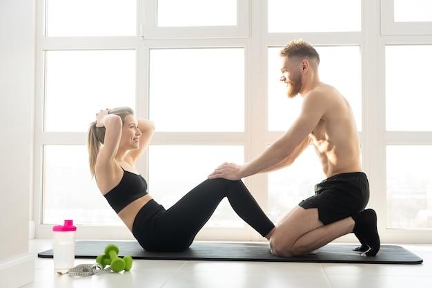 Fitnesstrainer helpt meisje kraken voor buikspieren op fitness mat. blonde vrouw draagt sportkleding. man met naakte torso. concept van sportactiviteit thuis. interieur van ruim appartement